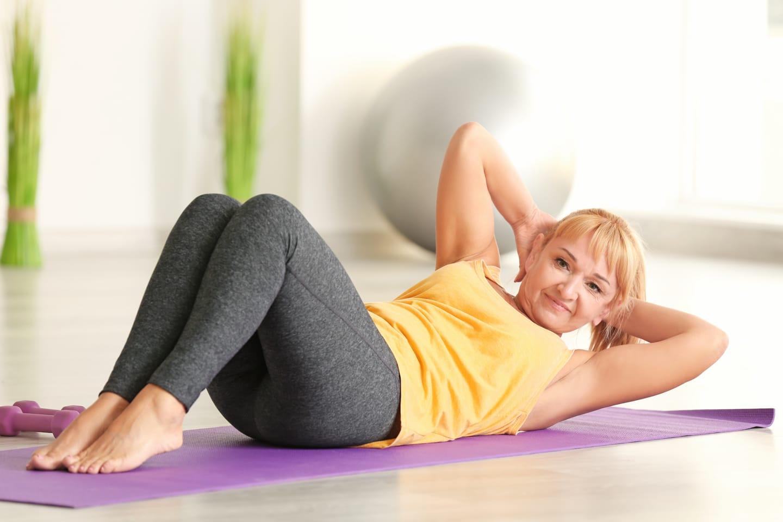 Reife Frau auf Boden mit Yogamatte Situps bei PZG Kurs Ladys 1st Frauenfitness Potsdam