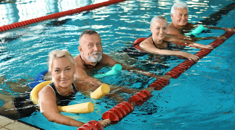 Frauen und Maenner in Wasser mit Schwimmhilfe bei Kurs Aquafitness Ladys 1st Potsdam