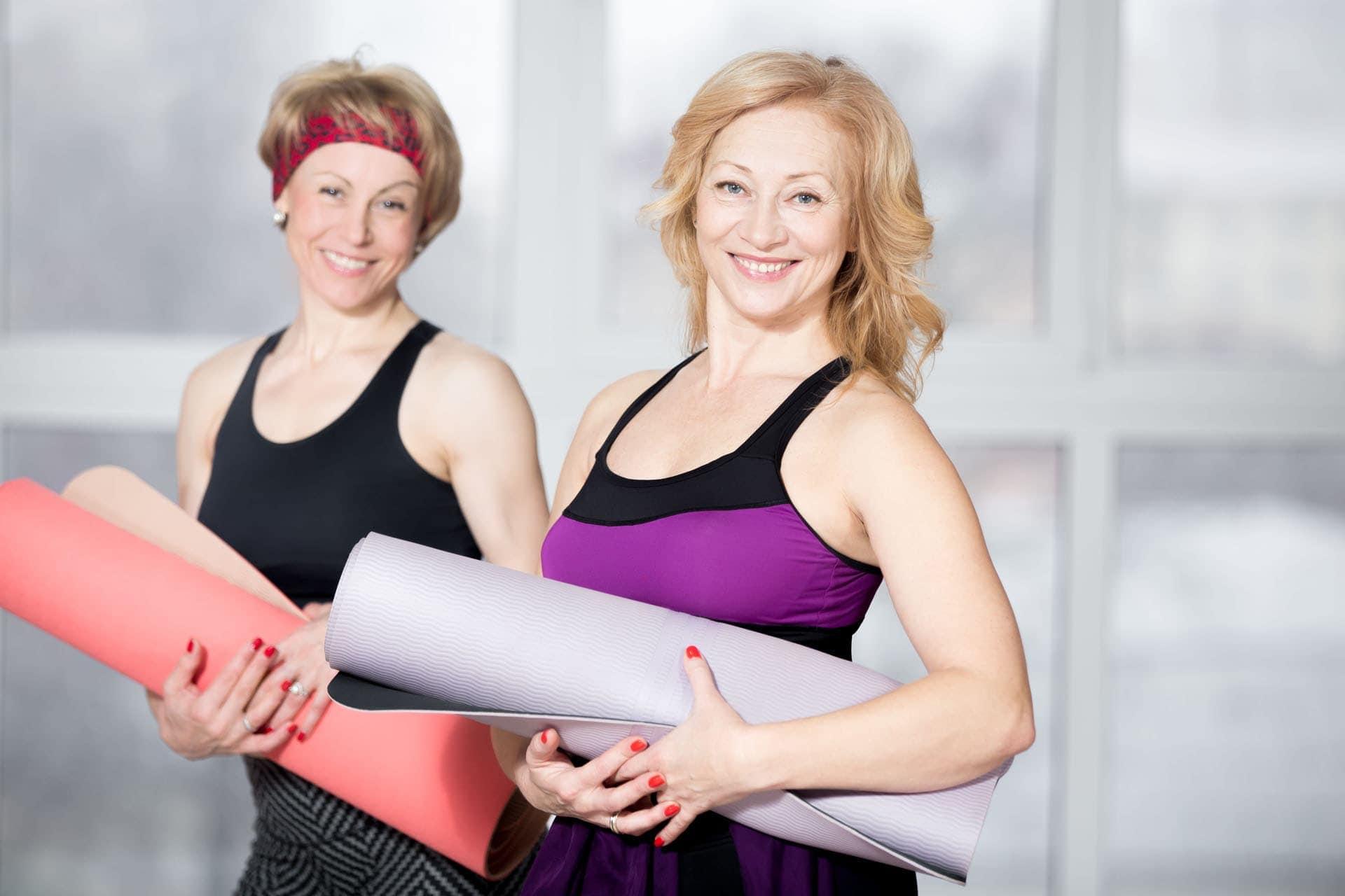 Frauen mit Yogamatte vor Fatburner Workout im Ladys 1st Frauenfitness Potsdam