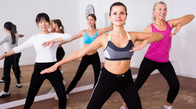 Gruppe junger Frauen trainiert mit Anleitung von Trainerin bei Trainingsangebote Zumba Kurs Ladys 1st Frauenfitness Potsdam