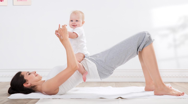 Mutter liegt mit Kind auf Rücken bei Trainingsangebote Fit mit Baby Kurs Ladys 1st Frauenfitness Potsdam