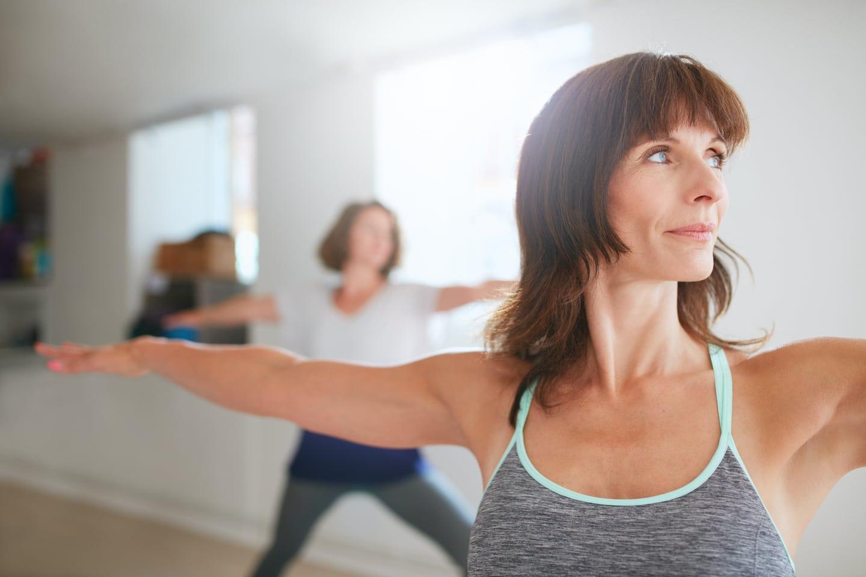 Reife Frau hält mit ausgestreckten Armen Balance bei Pilates Kurs Ladys 1st Frauenfitness Potsdam