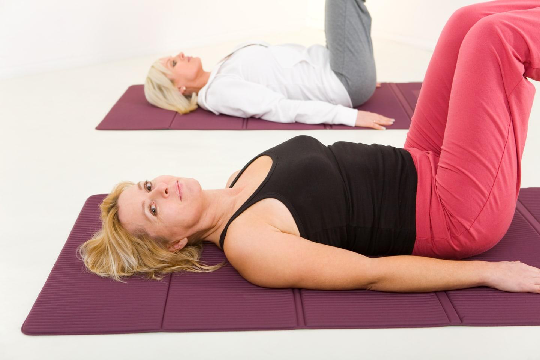 Frauen auf Boden mit Yogamatte und absolvieren Fatburner Kurs im Ladys 1st Frauenfitness Potsdam