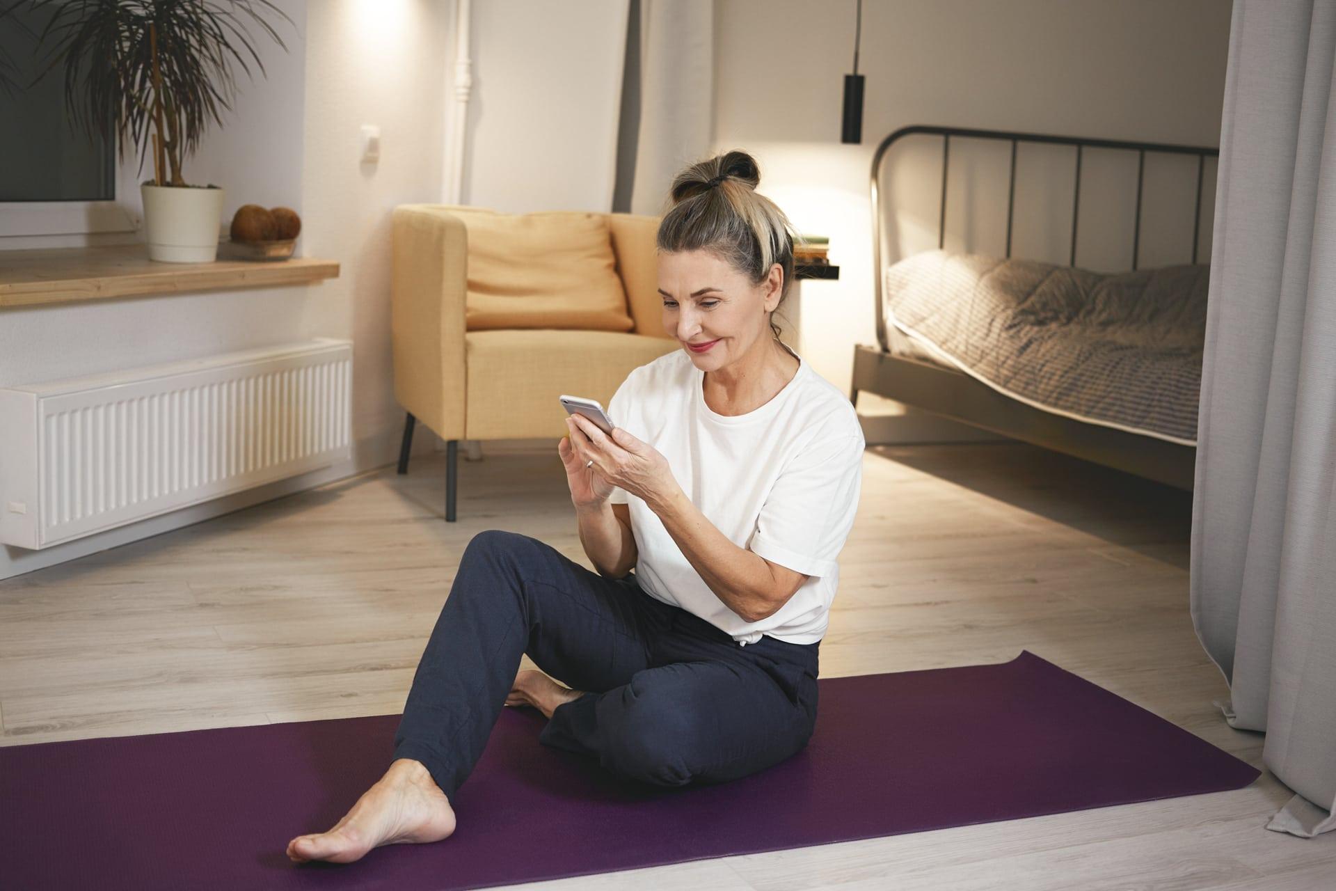 Seniorin mit Smartphone Zoom-Kurse Online Workouts Ladys 1st Frauenfitness Potsdam